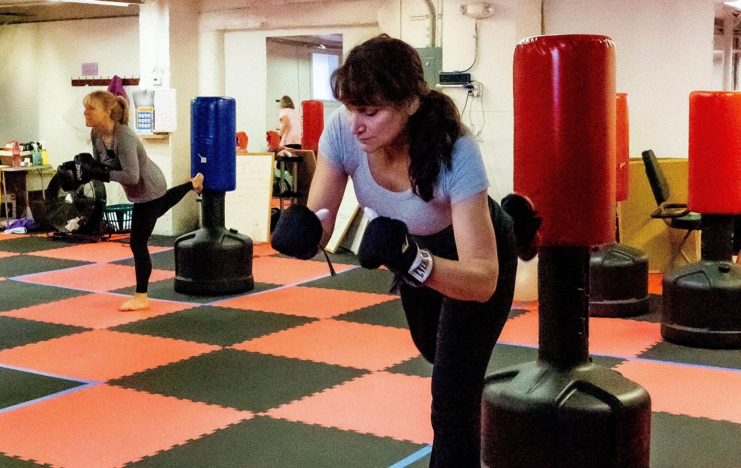 two woman kicking boxing bags
