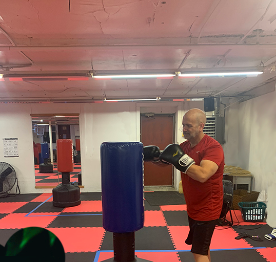 man punching blue boxing bag with black gloves
